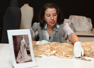 A conservator working on a dress