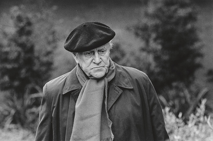 photo portrait taken outside of an elderly man in coat and scarf wearing a beret