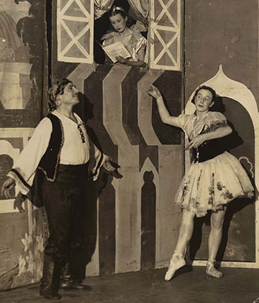 Three performers on stage. Two of them, a man and a woman in traditional folk costume, strike balletic poses while another performer reads a book in a window above their heads