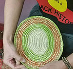 Cropped image of two hands holding a small circular woven mat