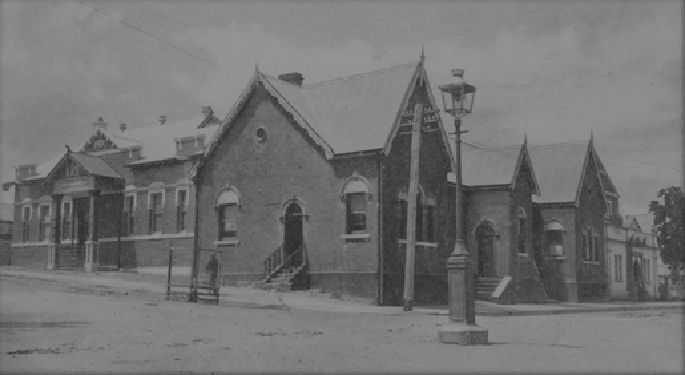 photograph of a building on the corner of an all-but deserted street. It looks like a large, rambling church hall