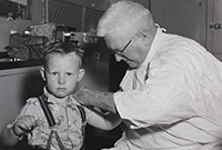 Interior black and white photo of a late middle-aged man in white coat administering injection to the upper arm of a boy, about five