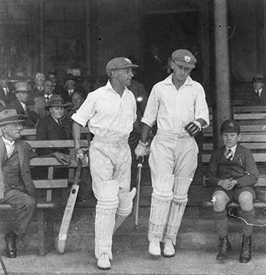 Two white-clad batsmen emerge from the stands with spectators on wooden benches on either side.