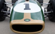 Detail showing part of racing car nose cone in dark green with gold trim.