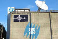 A building with the SBS logo and a large white satellite dish