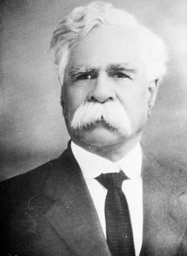 a black and white portrait photo of a white-haired man with a white moustache