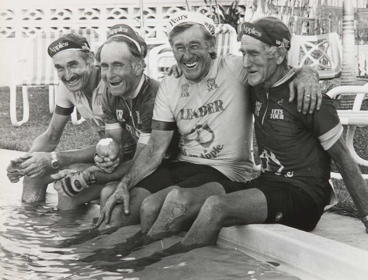 A black and white photo of Jim Coyle and his fellow riders sitting down with their feet in a pool of water. - click to view larger image