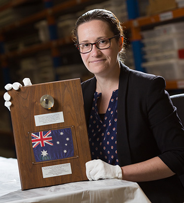 A Woman wearing white cotton preservation gloves, displaying wooden plaque mounted with a preserved object, a small Australian flag and labels printed or engraved with text.