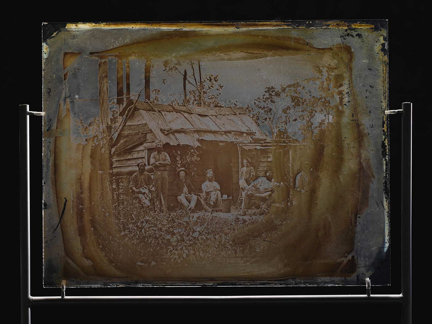 Glass showing seven men outside a bush slab hut. Most of the men are sitting and the man on the far right is only partially visible. - click to view larger image