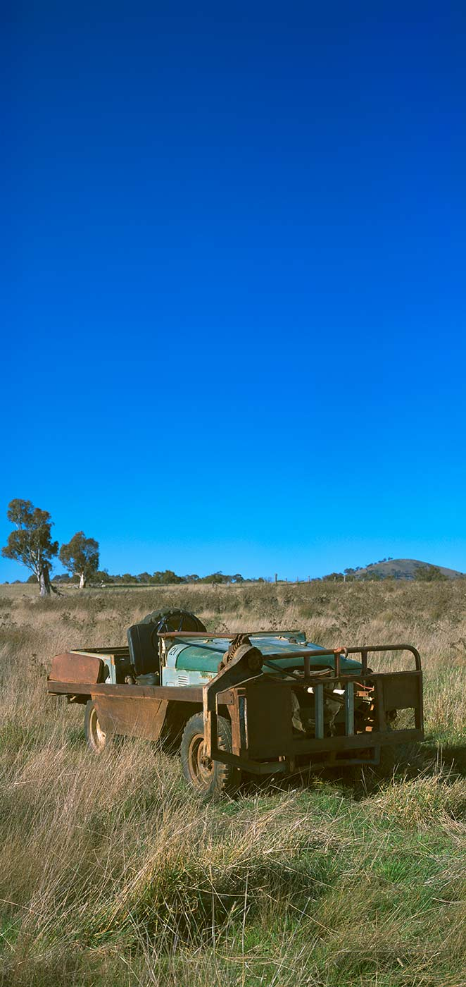 A rusty vehicle, made with modifications, parked in a grassy field with a bright blue sky in the background. - click to view larger image