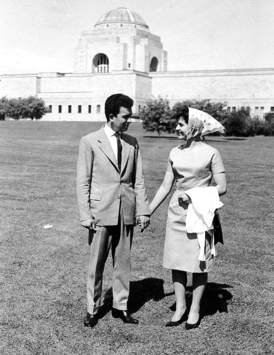 A black and white photo of a man and woman holding hands in. They are outdoors, standing on a lawn with a large white building in the background. - click to view larger image