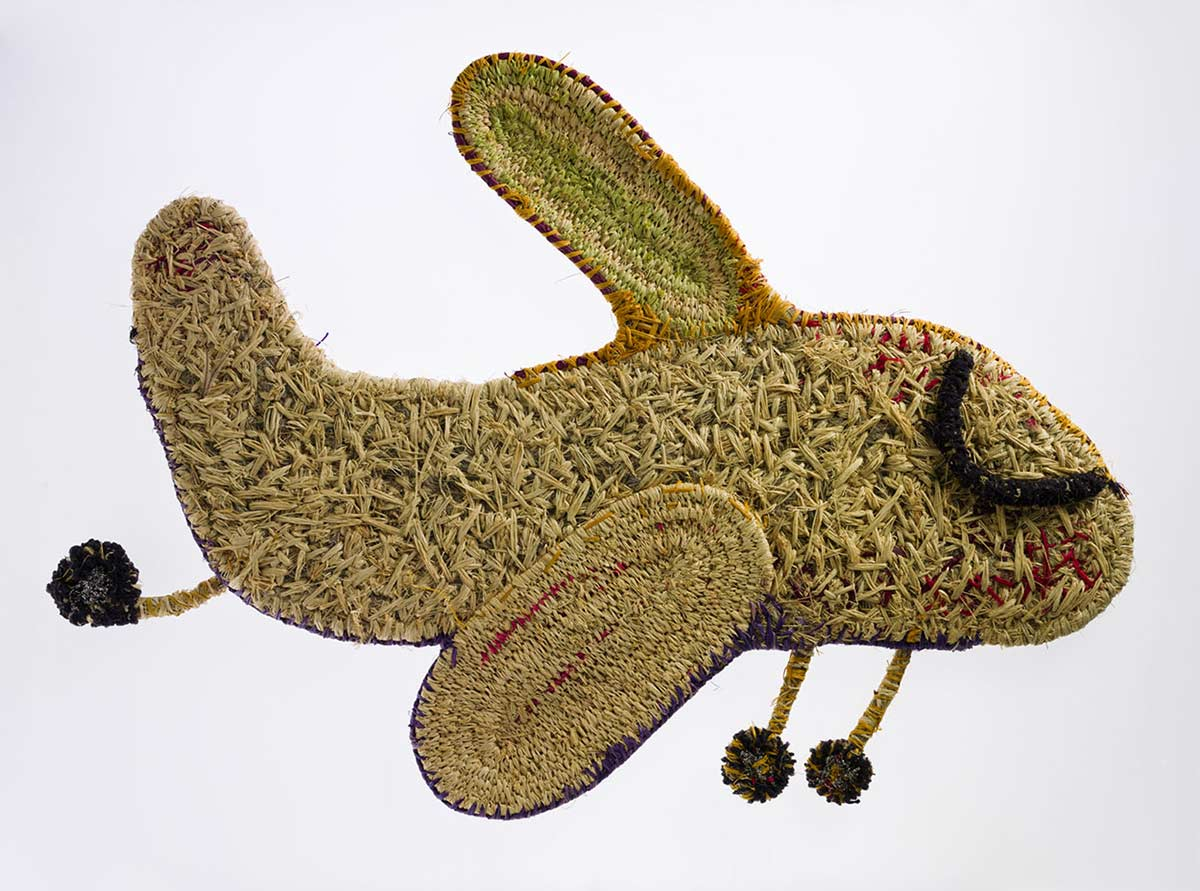 A sculpture depicting an aeroplane with its wheels down. The sculpture is made of woven grass, plant material dyed in different colours, wool and metallic thread. - click to view larger image