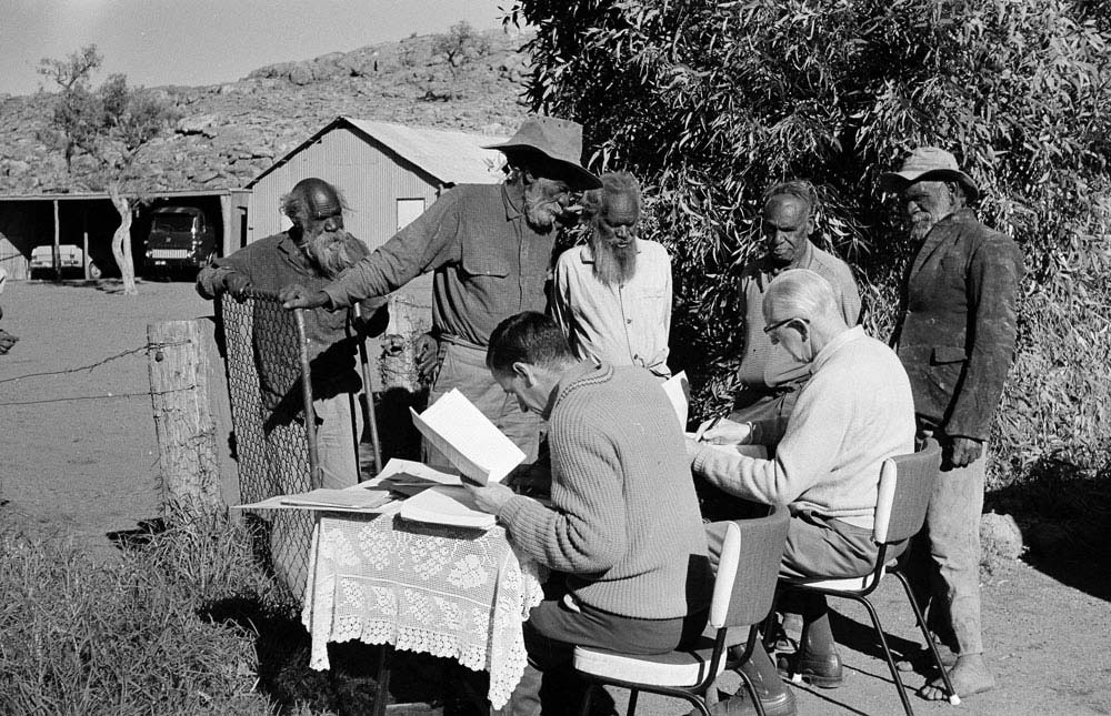 Black and white photo of a group of men standing around two seated male officials who are entering information into ledgers.
