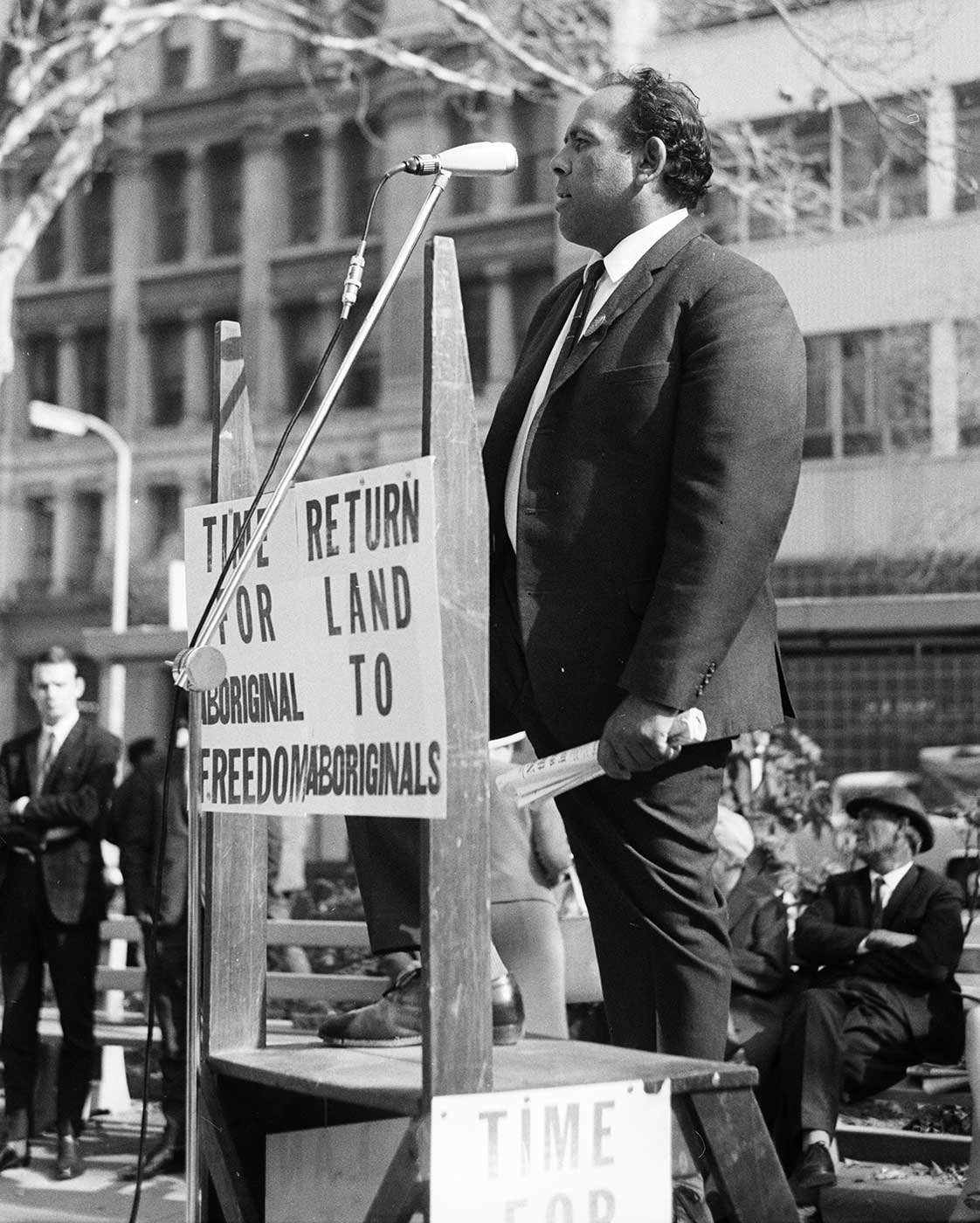 The placard refers to land. The speaker is Aboriginal trade unionist, Ray Peckham.