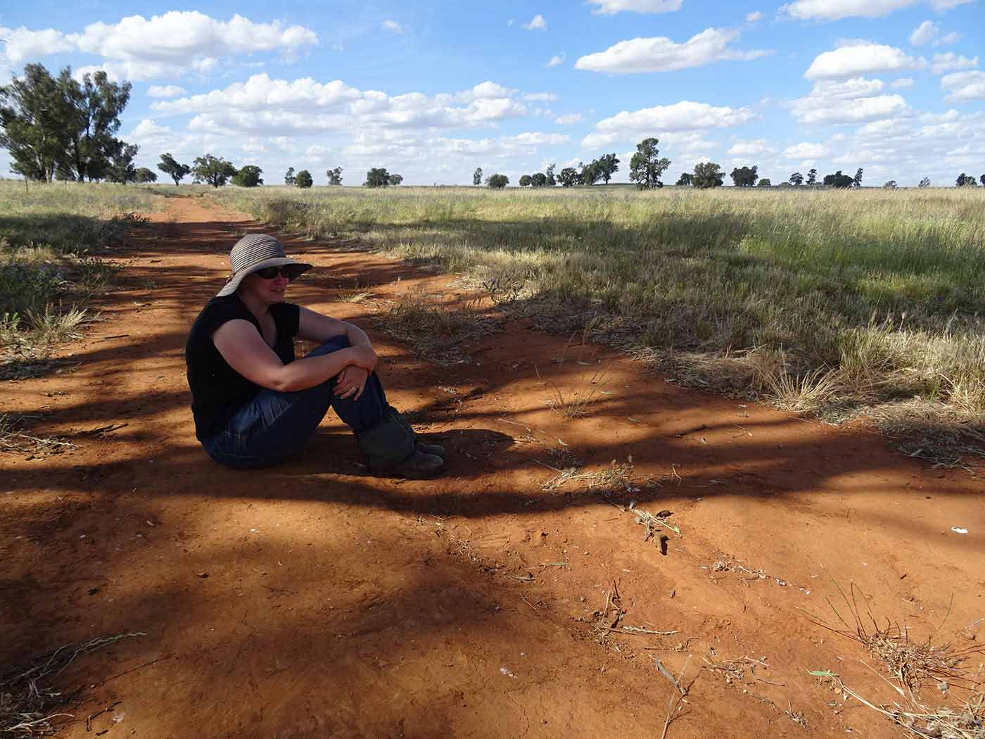 A woman sits on a path of red earth, in a paddock.