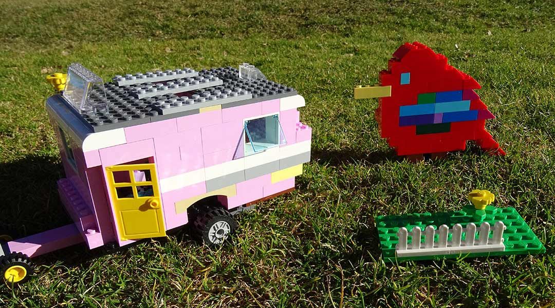 A model pink caravan and red bird made from LEGO bricks. - click to view larger image