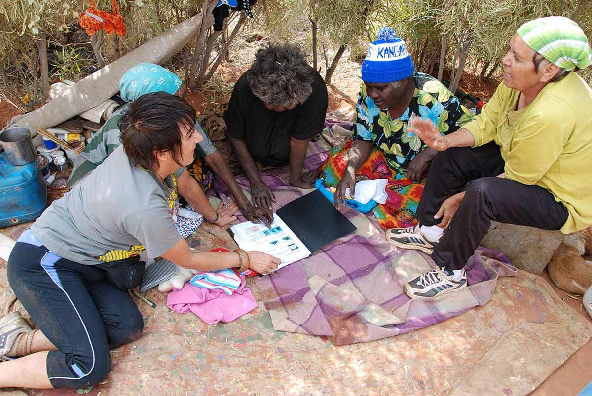 Five women sitting on the ground looking at a notebook of plans for the exhibition, Utopia: The Genius of Emily Kame Kngwarreye. Their camping gear can be seen in the background. - click to view larger image