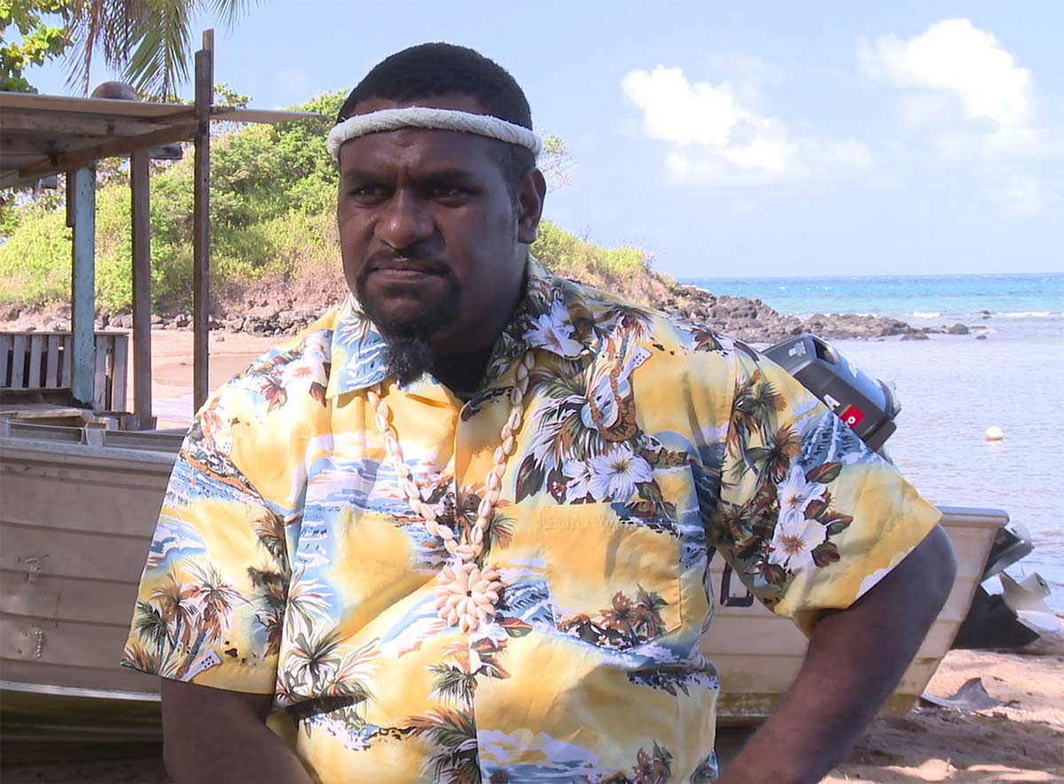 Photo of a man on a beach and wearing a white headband and a shirt with tropical motif.
