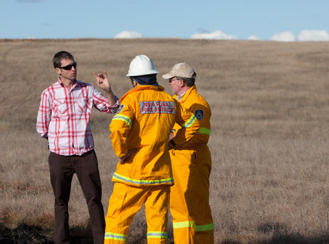 A colour photograph of three men standing in an open grassy field. Two of the men wear bright yellow fire crew clothing, and stand in the middle foreground. One has his back to the camera, while the other can be seen in profile as he faces the left of the photograph. The third man wears dark trousers and a light shirt with a check pattern on it. He stands further to the left, facing the other two men. In the background is part of the grassy field. It slopes up and away from the men. In the distance can be seen some of the sky and the tops of a few clouds.