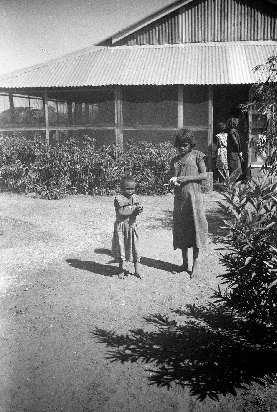 Two girls standing in front of the superintendent's house, Hooker Creek 1953-54. - click to view larger image