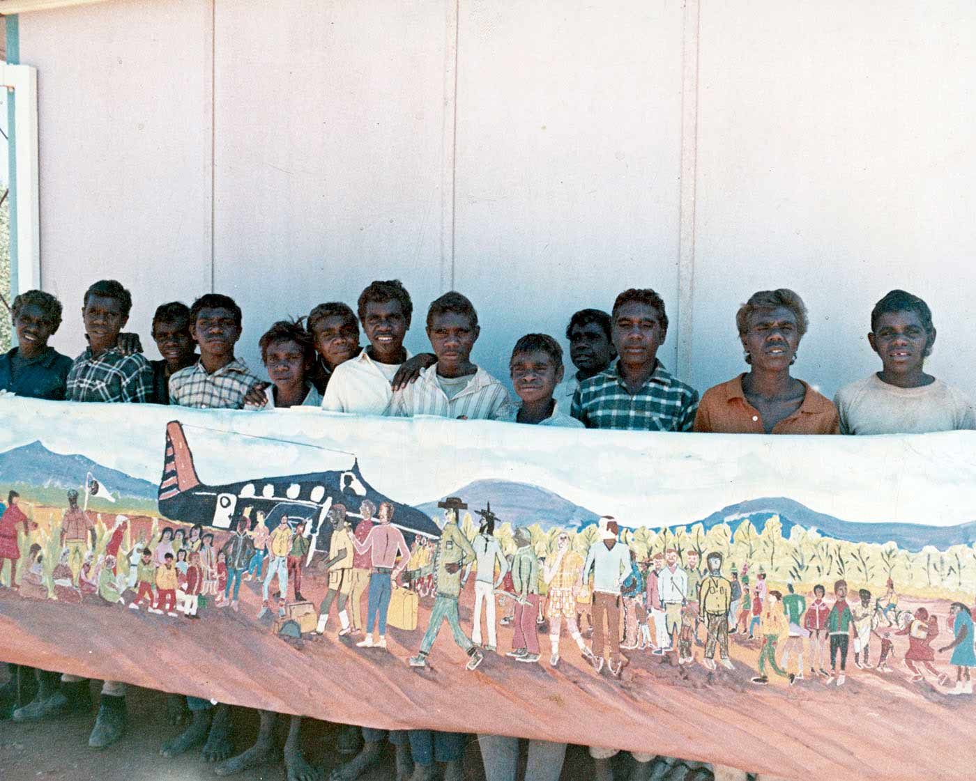 A  photo of a group of boys holding a painting.