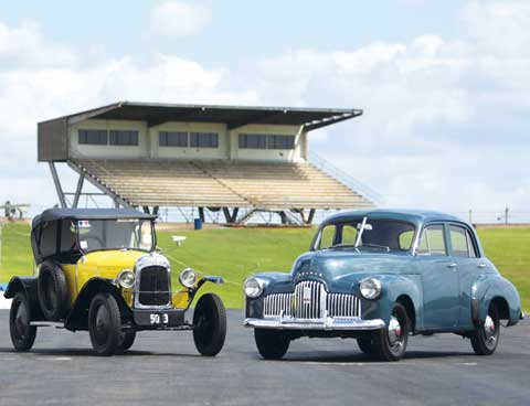 A 1923 5CV Citroën car, with yellow bodywork and black roof, and the blue-grey 1946 Holden Prototype No. 1 sedan at the Oran Park raceway. A grandstand is visible in the rear.