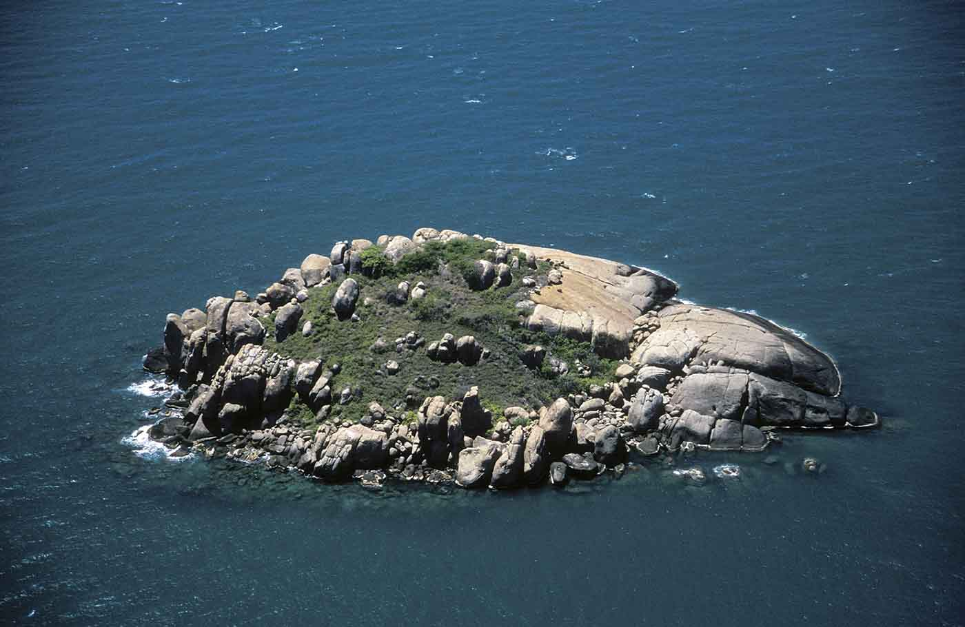 A colour photograph of a small rocky island surrounded by water. The photograph has been taken from an aeroplane. The island is mostly rock, except for a small patch of grass. The rock varies in colour from grey to a pale sandstone. The water around it is blue, with a few scattered white caps on the surface.  - click to view larger image