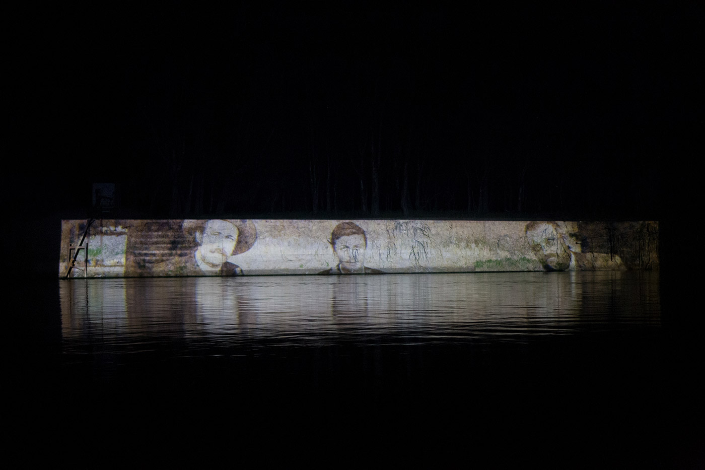 An image of wheat breeders Nathan Cobb, Fred Wills and William Farrer at Lambrigg (about 1892) projected onto the bank of the Murrumbidgee, 2015 - click to view larger image