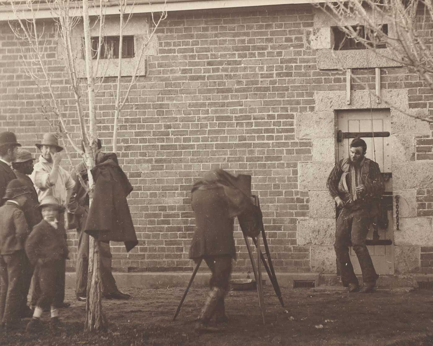 Black and white photo of a filming scene where a man is being filmed with a people looking on.