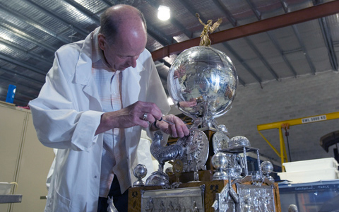 Medium distance shot of a conservator working on a silver trophy. The conservator, wearing a white lab coat, is on the left side of the image facing the camera but with his face turned towards the object. The object, on the right is a large silver globe with Australia in relief and clearly visible. A golden figurine perches on the top of the globe and various figures of animals are at the base of the trophy.