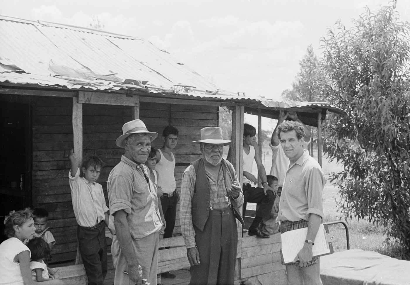 Black and white photo of a group of people standing around and in front of a wood shack. One man is holding a clipboard and appears to be in discussion with two other men.