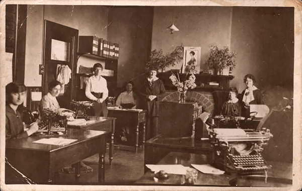 A black and white photograph of seven women in an office. Some have typewriters in front of them, some are standing, and all are looking at the camera. In the back left corner there are some box files on the top shelf of a set of shelves. Next to the shelves is a closed wooden door with a small glass panel in the top. There is a fireplace in the back wall with what appears to be a calendar propped up in the centre of the mantelpiece and a vase of flowers on each end. Another vase of flowers sits on top of a desktop filing unit on the right.  - click to view larger image