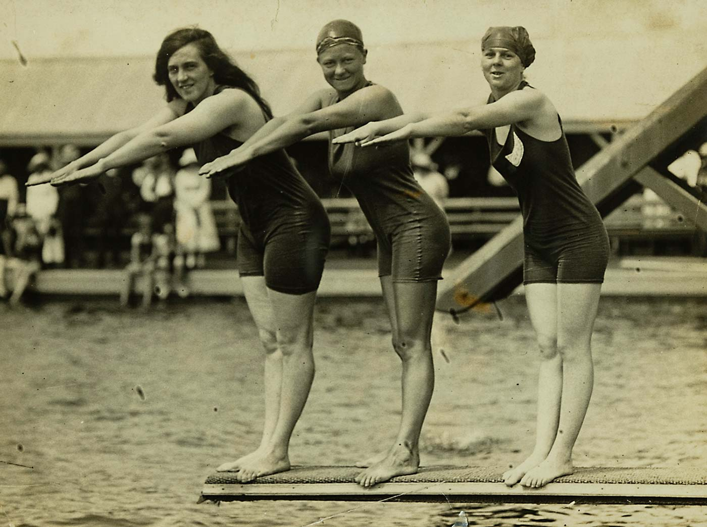A black and white photo of Fanny Durack, Mina Wylie and Jennie Fletcher dressed in swimming costumes and standing with arms outstretched on a diving board above a swimming pool.