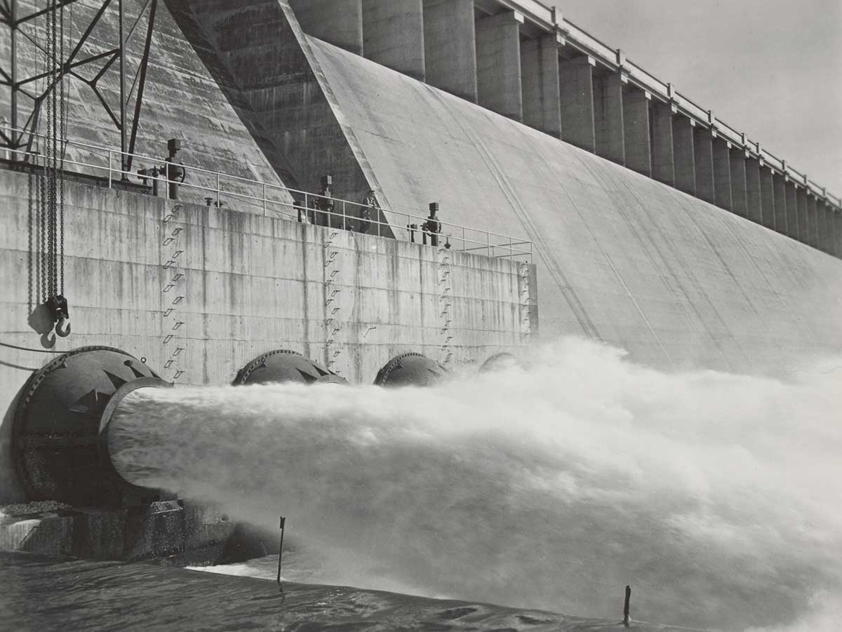Black and white photograph of a dam releasing water. - click to view larger image