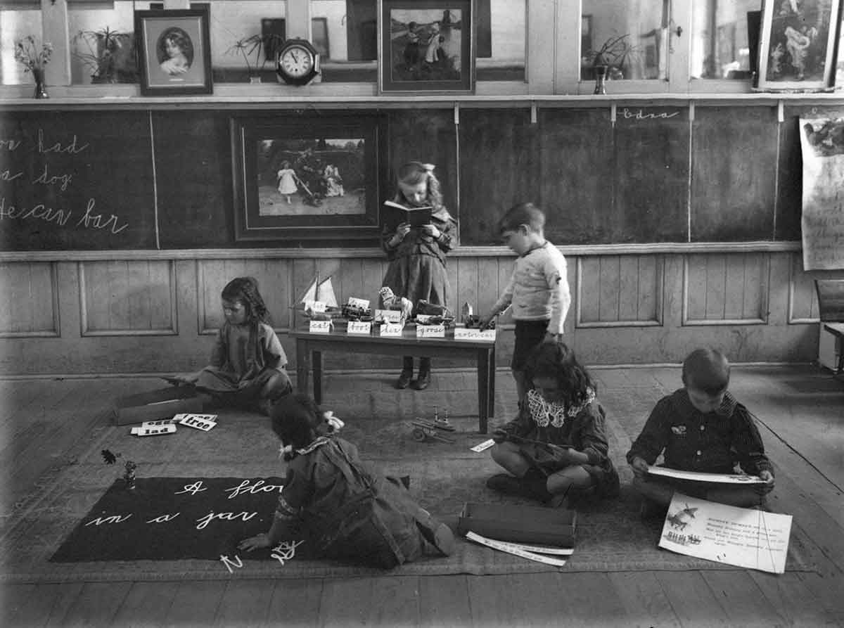 Black and white photograph of six children in a classroom. There are no desks in the classroom, with the children sitting and standing as they read and play.