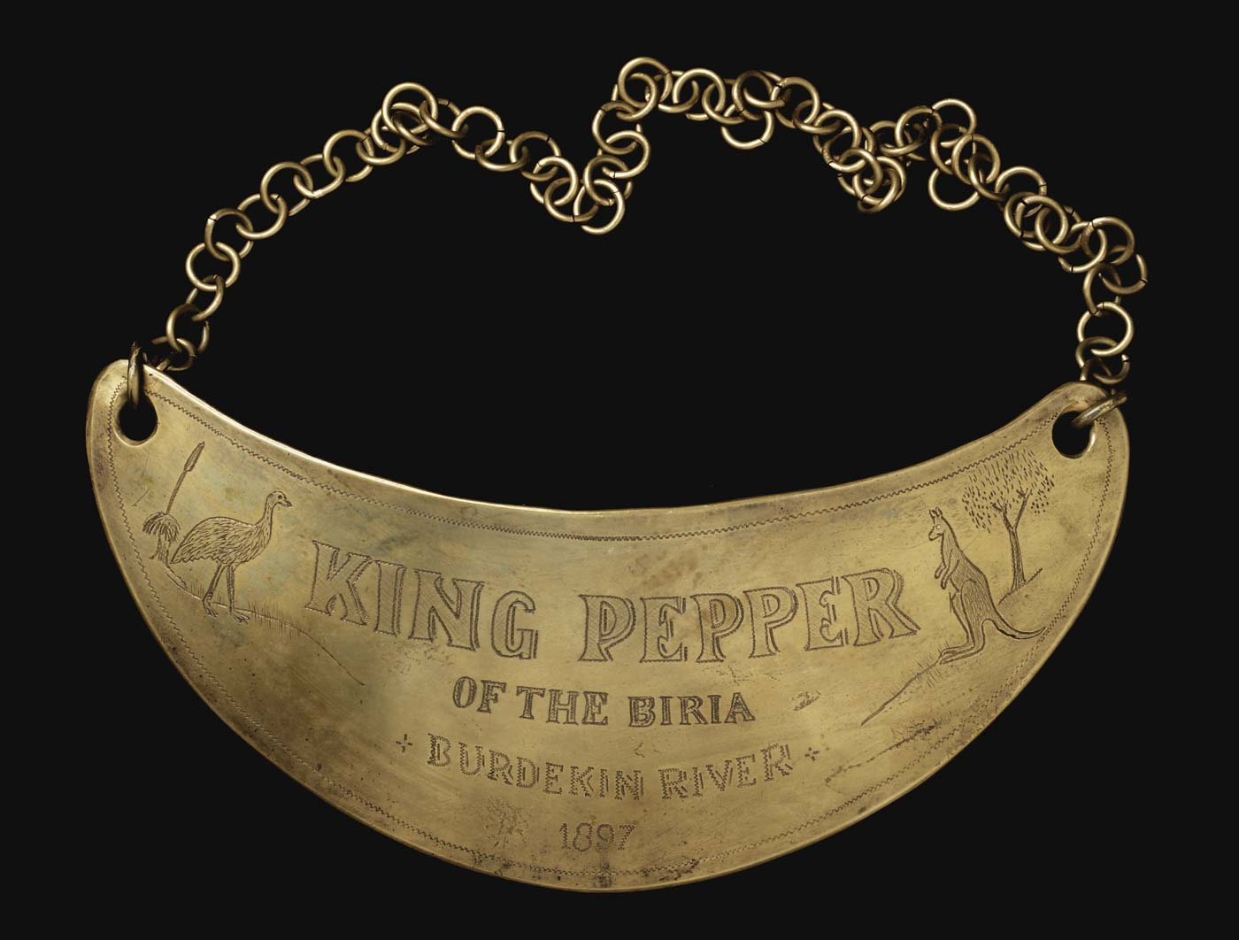 Crescent-shaped plate engraved with text 'King Pepper of the Biria, Burdekin River, 1897'. Includes engraved images of an emu and kangaroo, tree and plant. - click to view larger image