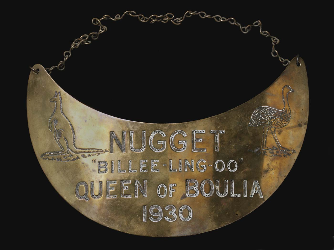 Crescent-shaped breastplate, with chain at top, engraved with an image of kangaroo and emu, and text: 'Nugget, 'Billee-ling-oo', Queen of Boulia, 1930'. - click to view larger image