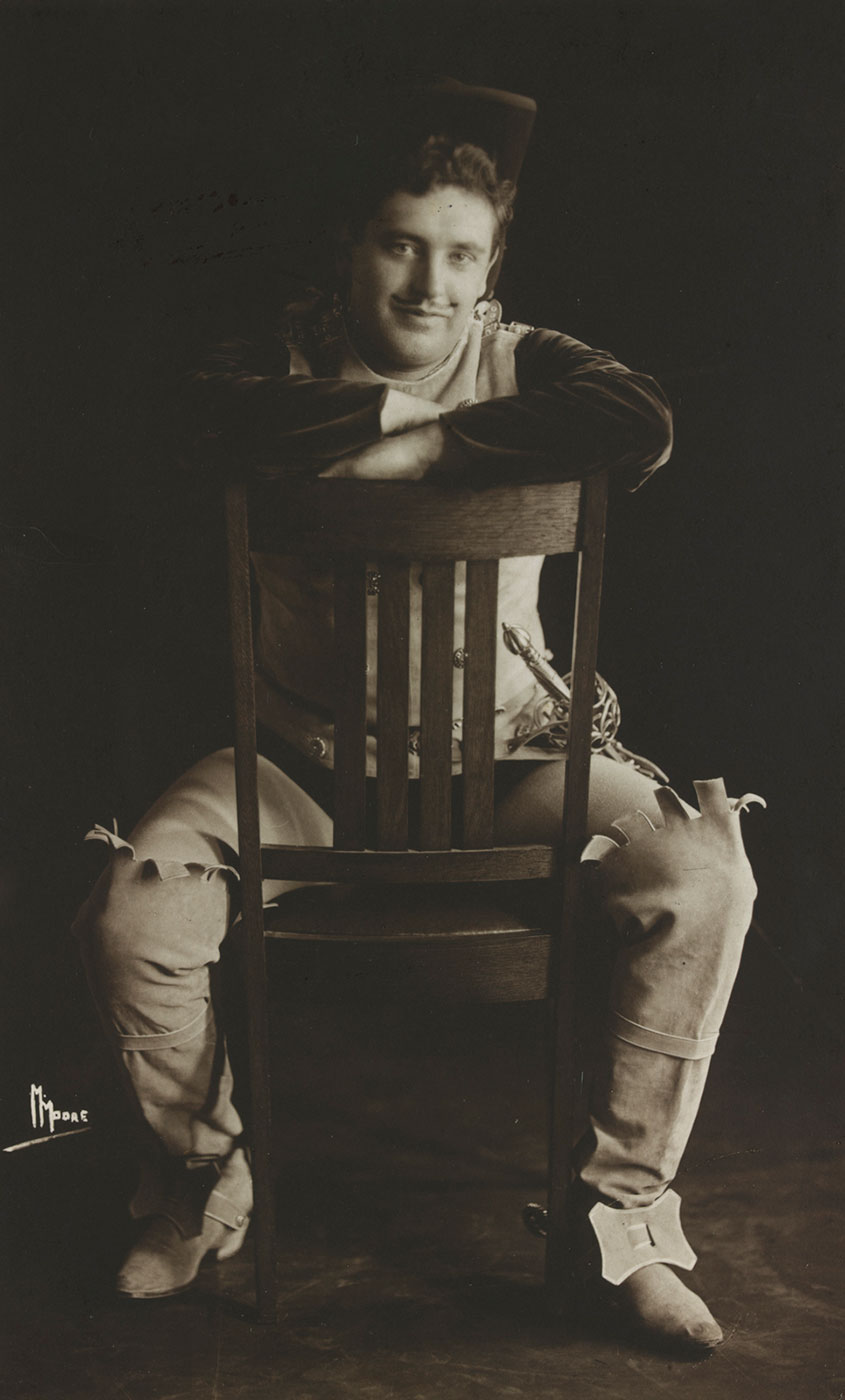 Photo of a man wearing a theatrical costume, leaning forward on to the back of a wooden chair.