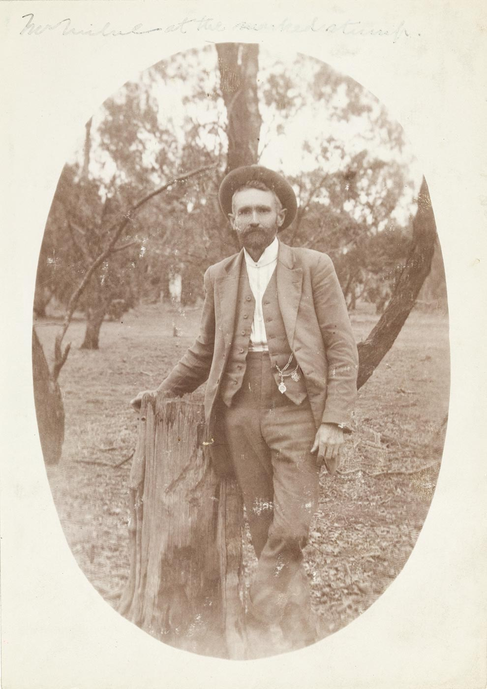 Black and white photo of a man leaning against a stump in bush land setting. - click to view larger image
