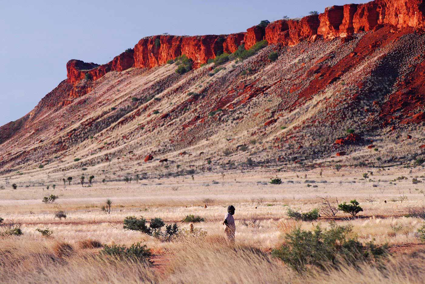 Colour photo of a landscape featuring a sloping mountain tapering to a red rock at the top.