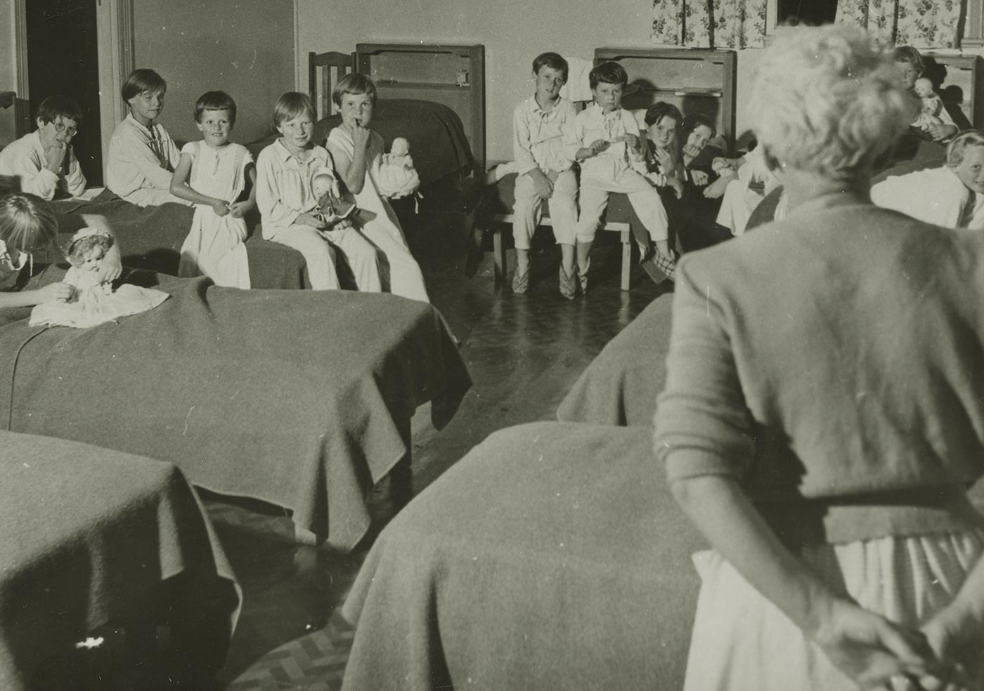 Black and white photo showing a group of 13 young girls sitting on beds watching a woman who has her back to the camera. The girls are dressed in pajamas and several of them hold dolls. - click to view larger image