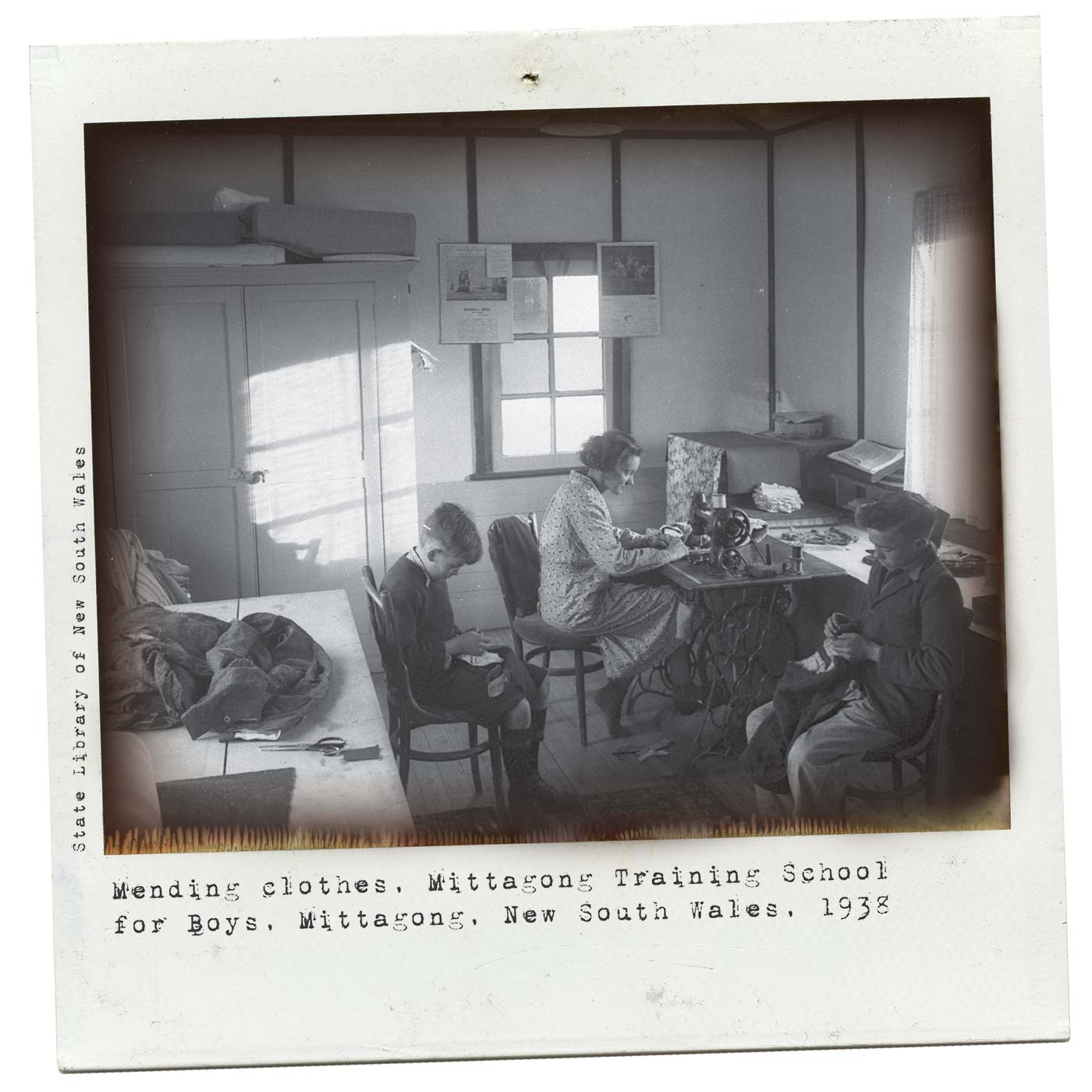 Polaroid photograph showing two boys sitting, stitching. A woman sits at a treadle sewing machine and several garments and a pair of scissors are on a table in the foreground. Typewritten text below reads 'Mending clothes, Mittagong Training School for Boys, Mittagong, New South Wales, 1938'. 'State Library of New South Wales' is typed along the left side. - click to view larger image