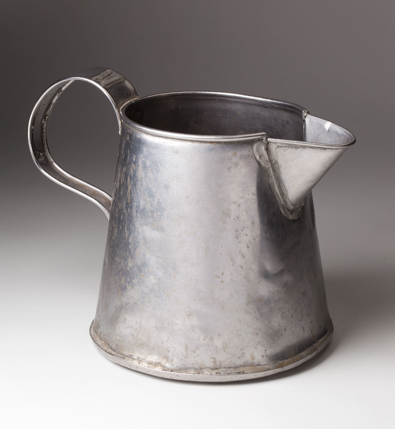 A silver-coloured metal jug with a rounded handle and pouring lip. - click to view larger image