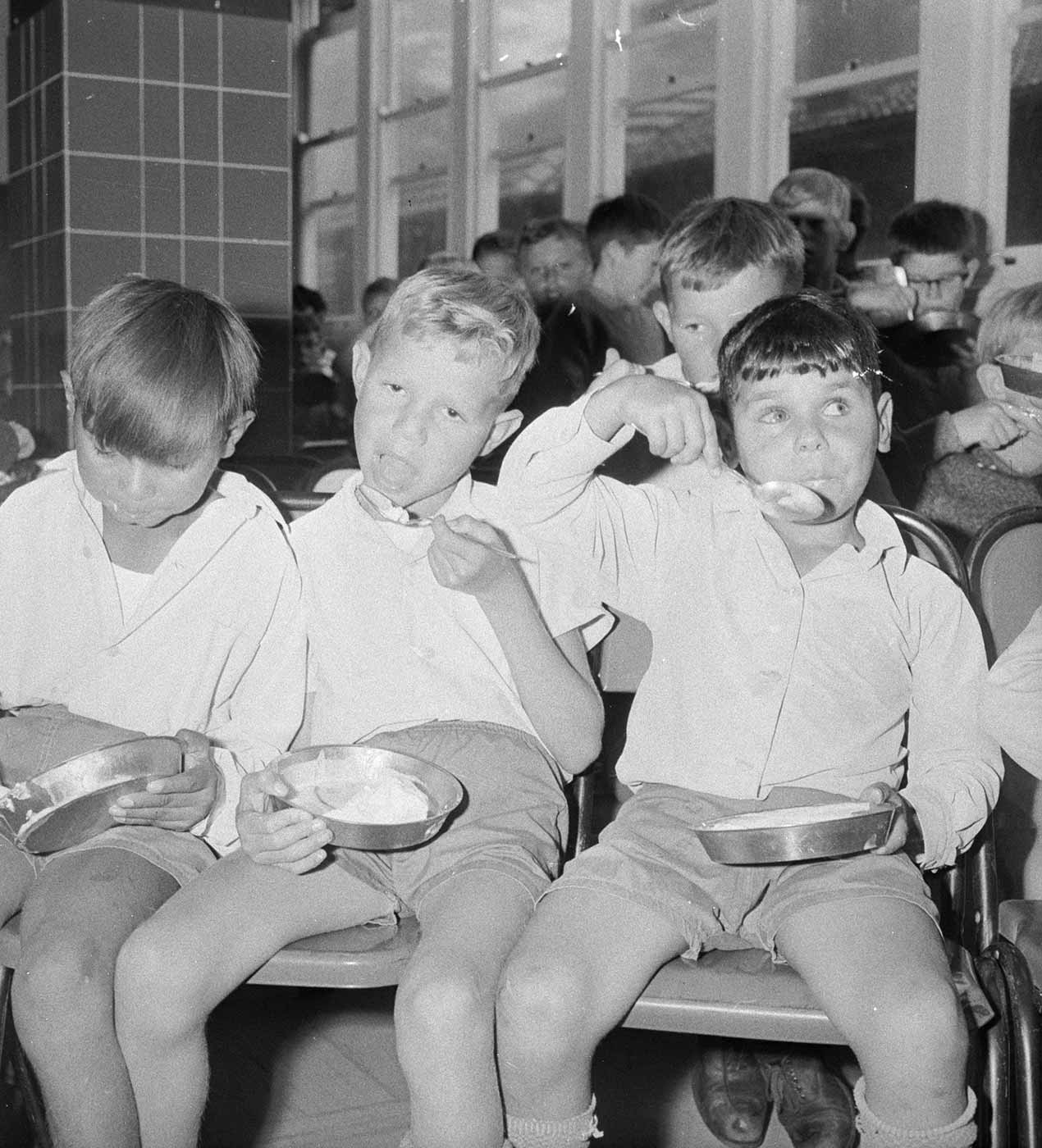 Black and white photo showing a group of boys, sitting eating from small metal bowls. - click to view larger image