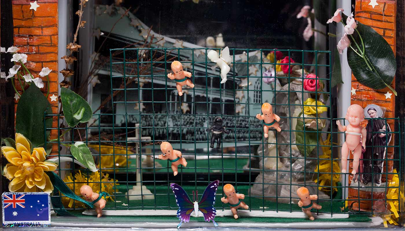 Close-up photo showing small plastic baby dolls tied to green wire netting. A black and white photo at the rear shows hundreds of children lined up in rows outside a building. Stars, leaves and flowers are seen at either side of the photo, and there is a butterfly at the centre. - click to view larger image