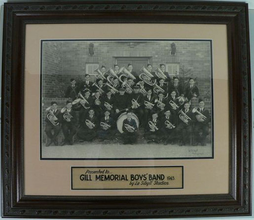 Framed formal black and white photograph showing a group of four rows of young boys, wearing uniforms, and holding brass instruments and drums. - click to view larger image