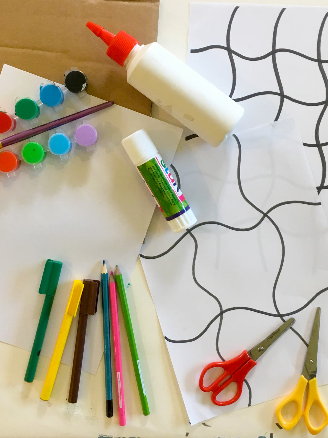 Craft materials including pencils, textas, paints, glue, scissors and a puzzle template.