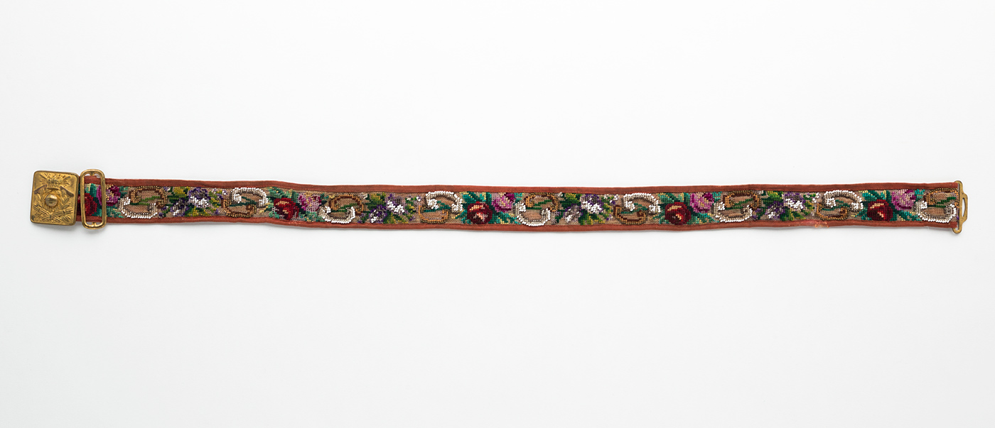 Belt of rust-coloured grosgrain backing and border, with central front strip of loose weave linen canvas gauze decorated with cross-stitch and beading with glass, haemitite and malachite beads. Pressed metal belt buckle with embossed crest consisting of crown bearing Maltese cross with two cricket bats crossed, a cricket ball in the centre and two sets of cricket stumps beneath. Metal sliding adjuster next to this and buckle hook at opposite end. Maker's stamp on buckle, consisting of a diamond shape divided into five sections containing