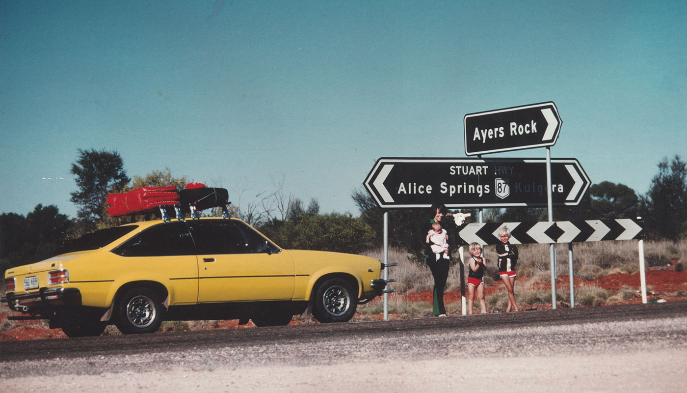 Colour photo showing a woman and three children in front of a road junction, with signs pointing to 'Ayers Rock' and 'Alice Springs'. Beside them is a bright yellow car.