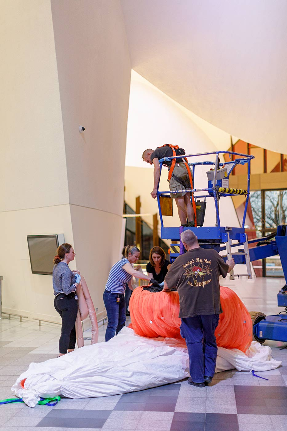 Colour photograph of staff installing a large object in a hall. - click to view larger image